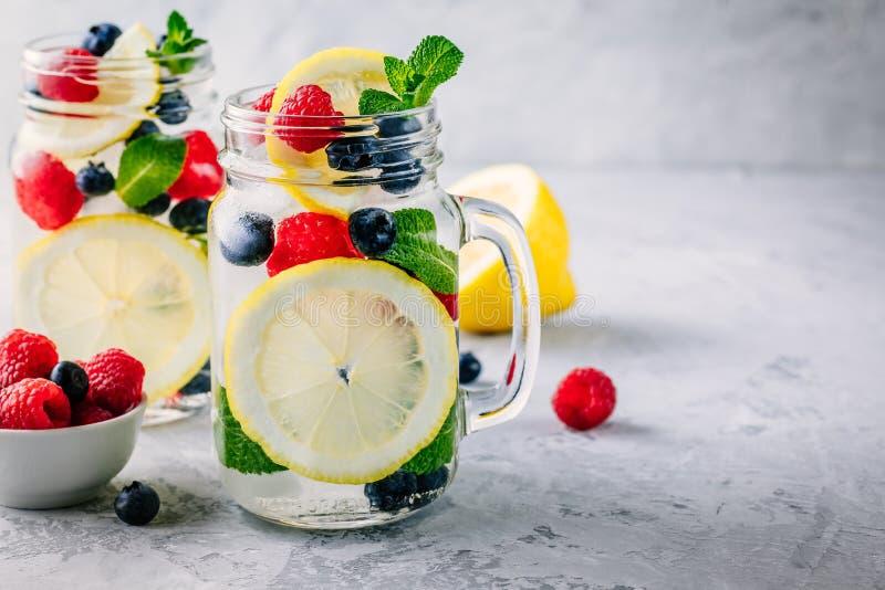 Gegoten detox water met citroenplak, framboos, bosbes en munt Ijskoude de zomercocktail of limonade in metselaarkruik royalty-vrije stock afbeeldingen