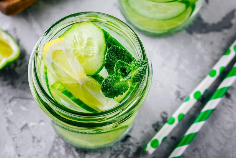 Gegoten detox water met komkommer, citroen en kalk Verfrissende ijskoude de zomercocktail of limonade in glas royalty-vrije stock afbeelding