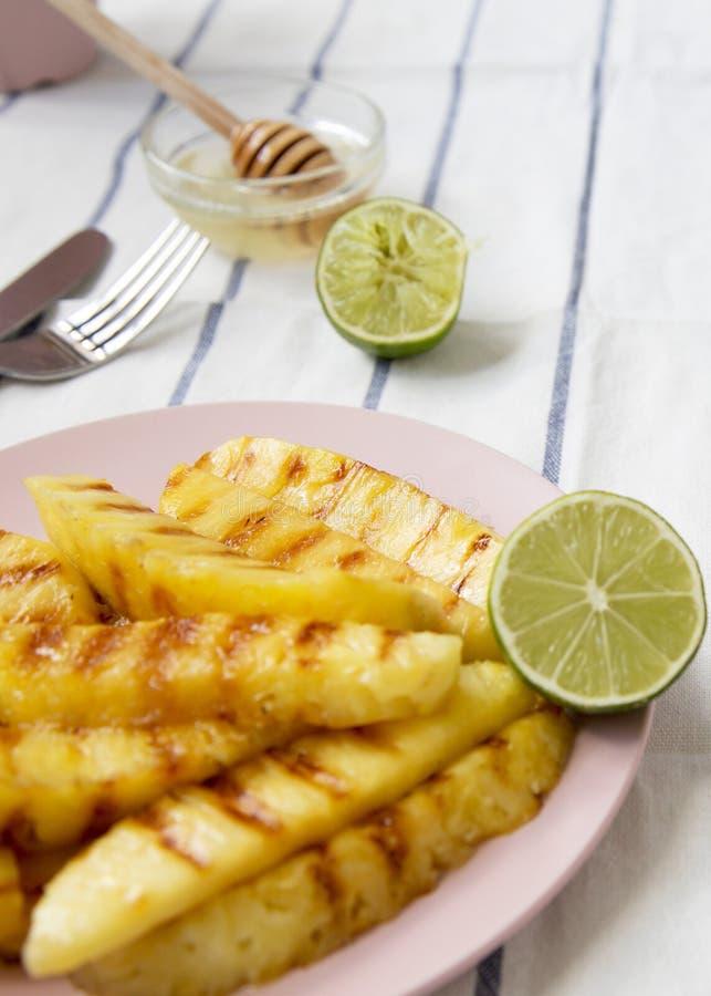 Gegrillte Ananasscheiben auf einer rosa Platte mit Honig und Kalk, niedriger Winkel Sommerlebensmittel Nahaufnahme Selektiver Fok stockfoto