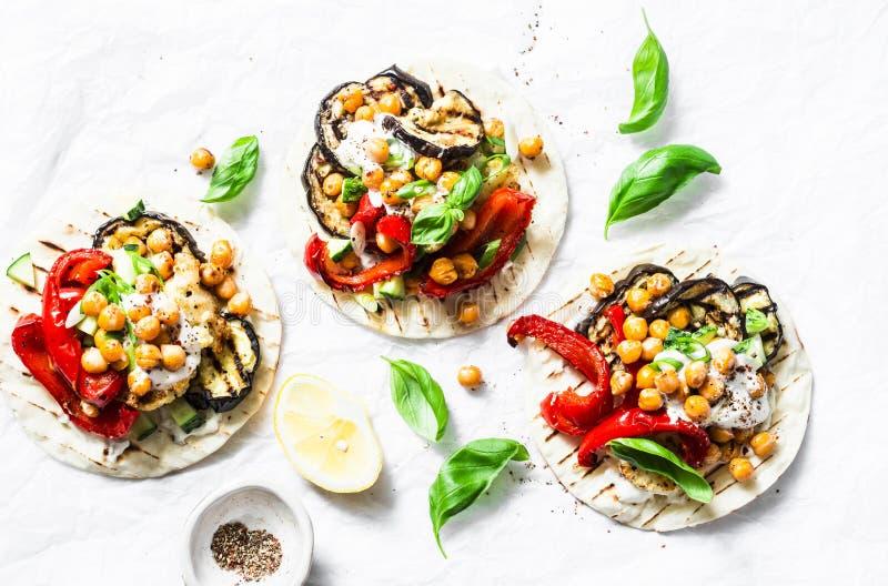 Gegrillte Aubergine, Gemüsepaprikas, Blumenkohl und vegetarische Tortillas der würzigen Kichererbsen auf einem hellen Hintergrund lizenzfreie stockbilder