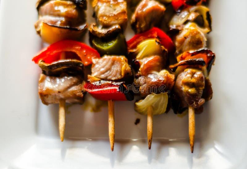Gegrillte Aufsteckspindeln des Fleisches und des Gemüses auf einem hölzernen Brett-, bunten und geschmackvollenteller lizenzfreies stockbild
