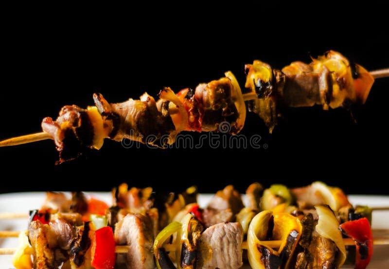 Gegrillte Aufsteckspindeln des Fleisches und des Gemüses auf einem hölzernen Brett-, bunten und geschmackvollenteller lizenzfreie stockfotografie