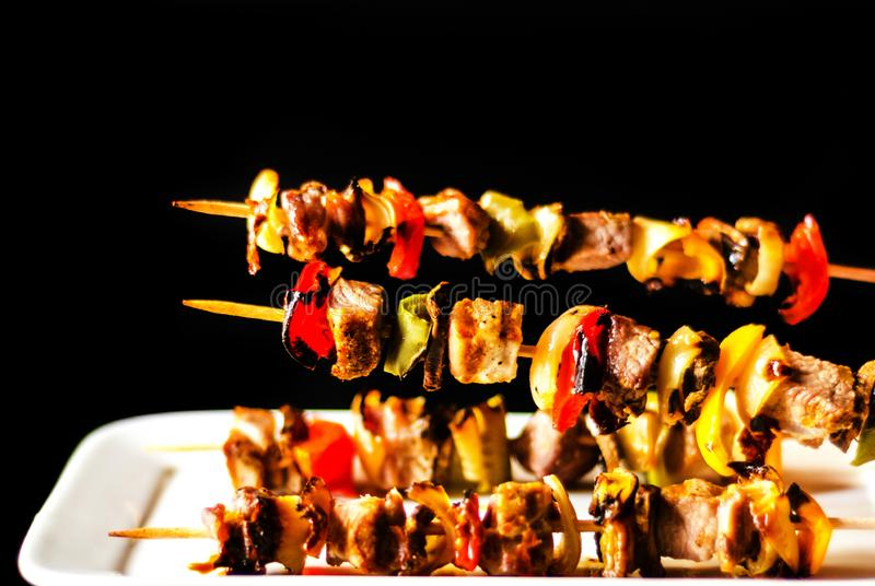 Gegrillte Aufsteckspindeln des Fleisches und des Gemüses auf einem hölzernen Brett-, bunten und geschmackvollenteller stockbilder