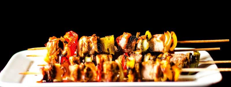 Gegrillte Aufsteckspindeln des Fleisches und des Gemüses auf einem hölzernen Brett-, bunten und geschmackvollenteller stockfoto
