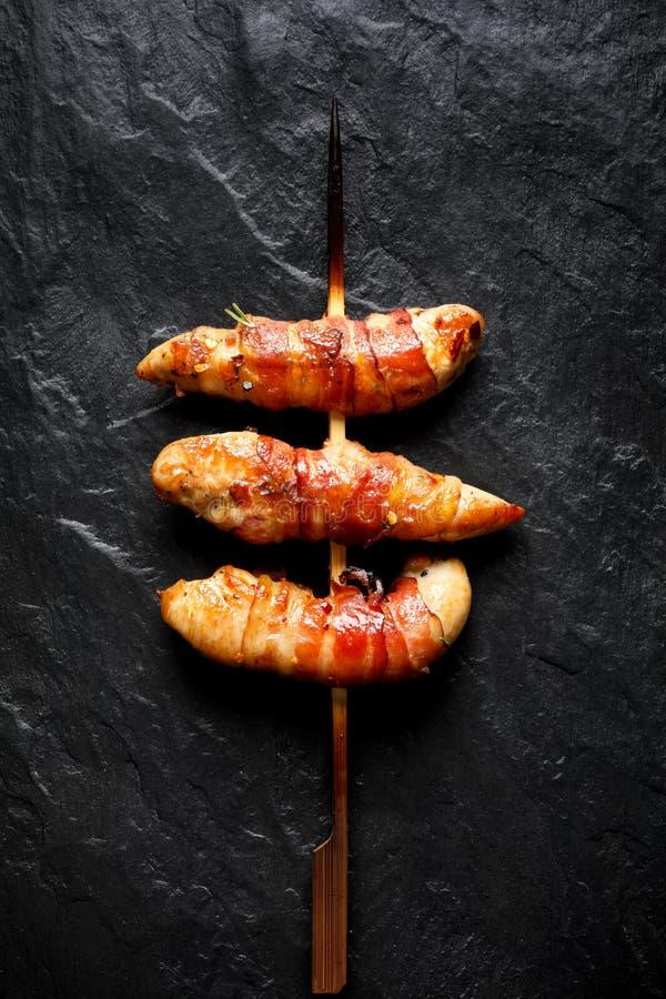 Gegrillte Aufsteckspindeln des Hühnerzarten lendenstücks eingewickelt mit Speck auf einem schwarzen Hintergrund stockfotos