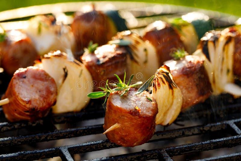 Gegrillte Aufsteckspindeln mit Würsten und Zwiebeln auf einer Grillplatte, nahes hohes im Freien lizenzfreie stockbilder