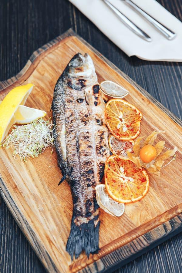Gegrillte Fische auf einem hölzernen Brett des Ausschnitts mit Scheiben der Orange und der Zitrone Hölzerner Hintergrund stockbild