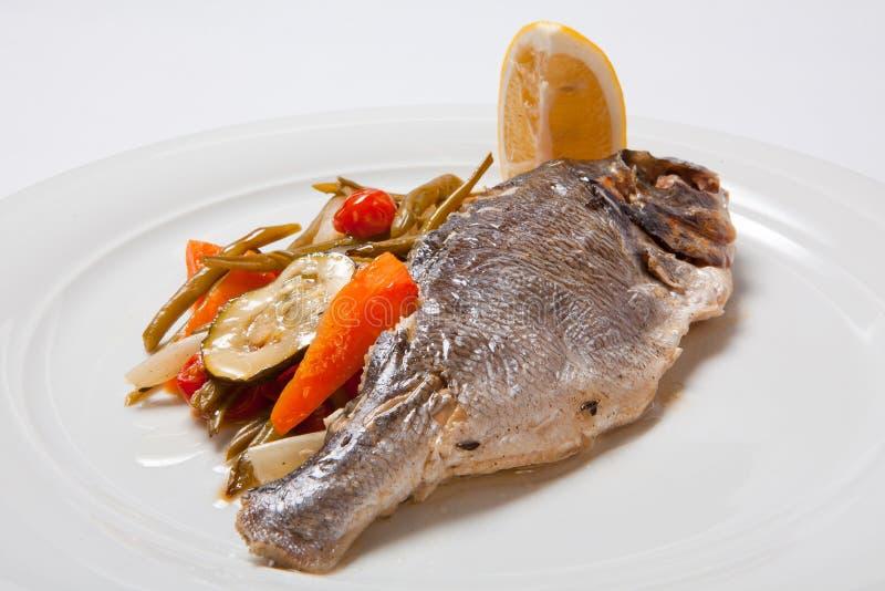 Gegrillte Fische mit gebratenem Gemüse auf der Platte stockbild