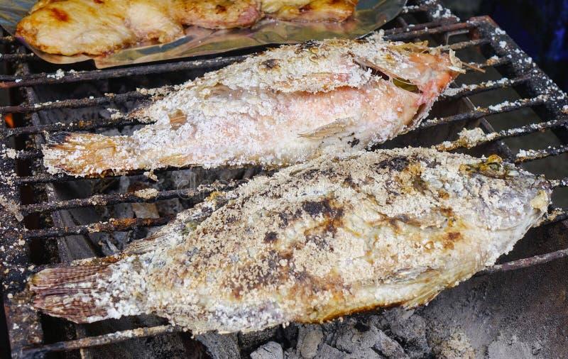 Gegrillte Fische mit Gewürzen auf Feuer lizenzfreie stockfotos