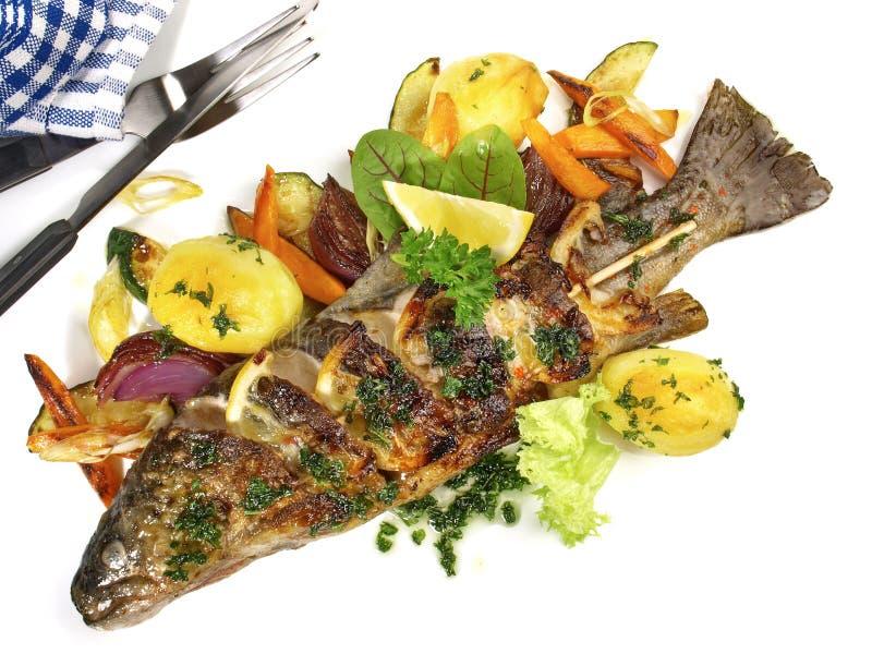 Gegrillte Fische - Regenbogenforelle mit Gemüse und Kartoffeln stockbild