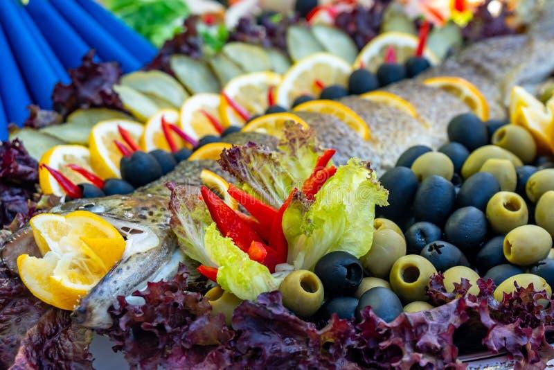 Gegrillte Forelle, Karpfen und Meer?sche Saftige Zartheitsfische auf einer Platte mit einem Salat des gebratenen Gem?ses Balkan-K lizenzfreie stockfotos
