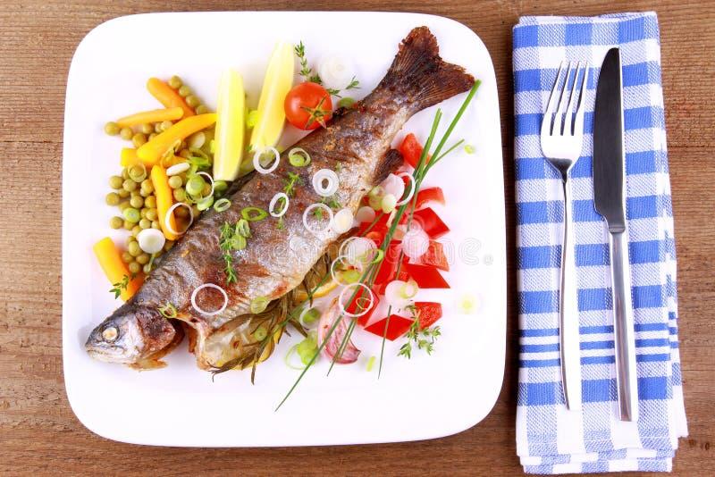 Gegrillte Forelle mit ziemlich unterschiedlichem Gemüse mit Tischbesteck stockfoto