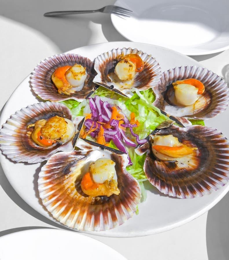 Gegrillte galizische Kammmuscheln, Meeresfr?chtesalat und Wei?wein auf wei?em backgound Iberische veränderte Kammmuscheln Zamburi stockbilder