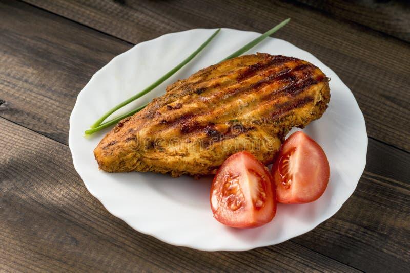 Gegrillte gesunde Hühnerbrust diente mit Tomate und frischem Schnittlauch stockbilder