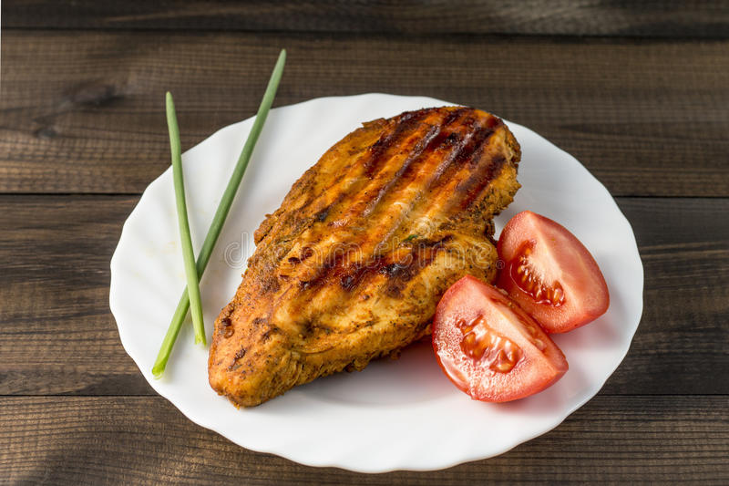 Gegrillte gesunde Hühnerbrust diente mit Tomate und frischem Schnittlauch auf weißer Platte auf Holztisch lizenzfreie stockbilder