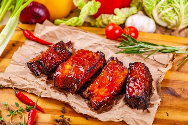 Gegrillte Grillschweinefleischrippen mit Gewürzen und Kräutern auf hölzernem Brett stockbild