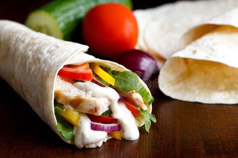 Gegrillte Hühner- und Salattortillaverpackung mit Isolat der weißen Soße stockfotografie