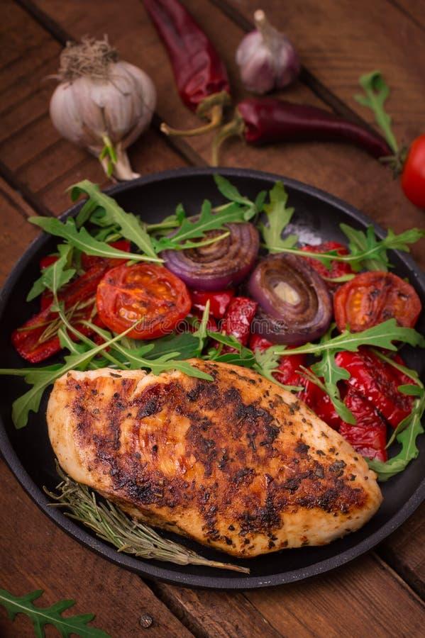 Gegrillte Hühnerbrust mit grünem Salat vom Arugula und vom Gemüse auf einer schwarzen Wanne Hölzerner rustikaler Hintergrund Besc stockfotos