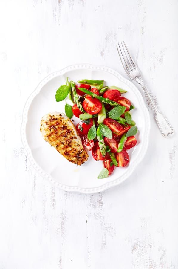 Gegrillte Hühnerbrust mit Spargel und Cherry Tomato Salad mit Kräutern und Chia Seeds lizenzfreie stockbilder