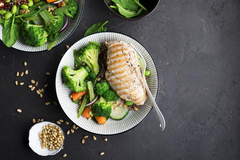 Gegrillte Hühnerbrust, roter Reis und frisches Brokkoligemüse, Karotten, Sojabohnen, Spinat für schmückt Mit Kiefernnüssen lizenzfreies stockbild