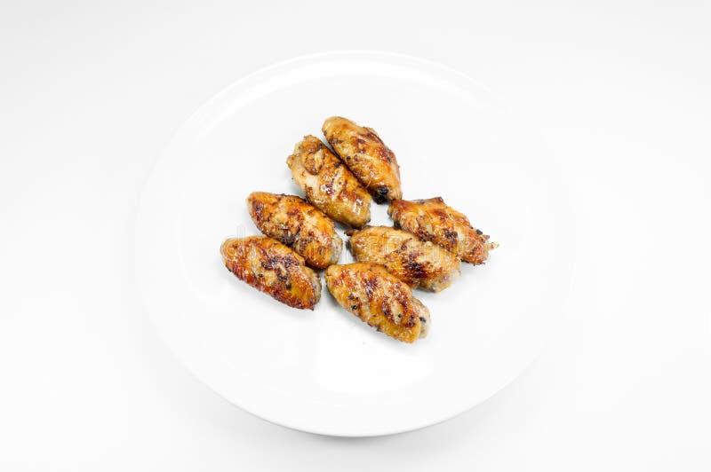 Gegrillte Hühnerflügel im Tellerweiß auf Weiß lizenzfreie stockfotos