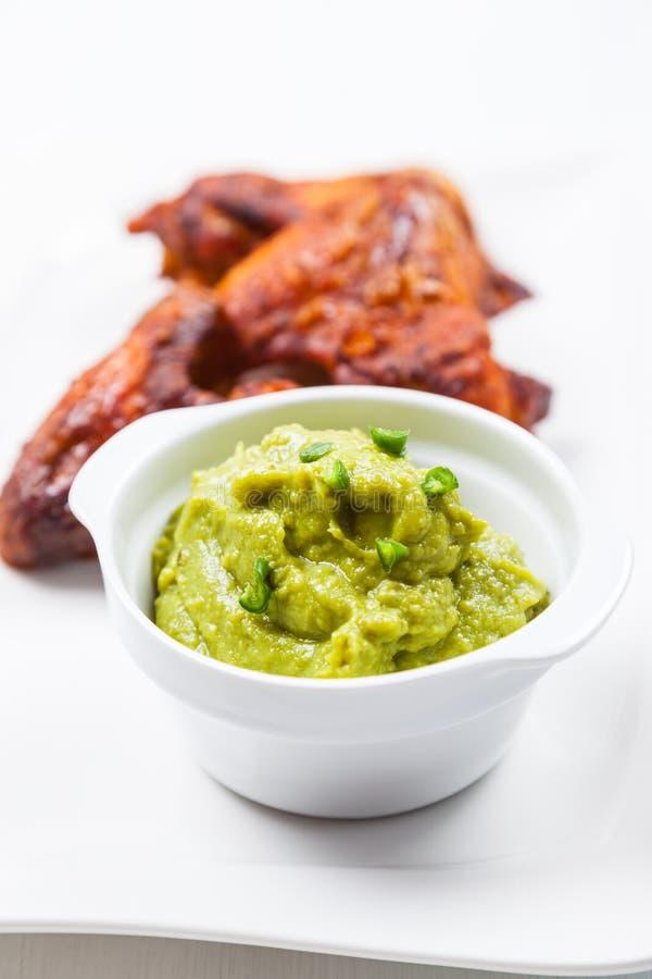 Gegrillte Hühnerflügel mit Guacamolen stockfotos
