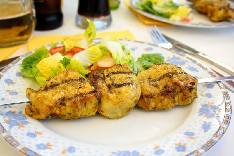 Gegrillte Hühnerleiste auf Metallaufsteckspindel mit Salat stockbild