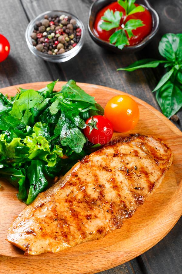 Gegrillte Hühnerleiste mit Frischgemüsesalat, -tomaten und -soße auf hölzernem Schneidebrett stockfotos