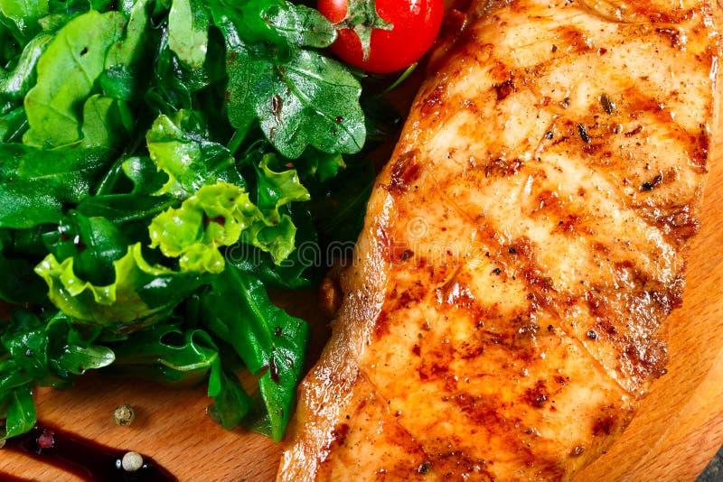 Gegrillte Hühnerleiste mit Frischgemüsesalat, -tomaten und -soße auf hölzernem Schneidebrett Heiße Fleischteller stockbilder