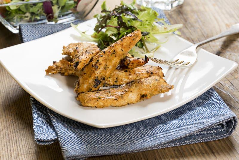 Gegrillte Hühnerstreifen mit Seitensalat lizenzfreies stockfoto
