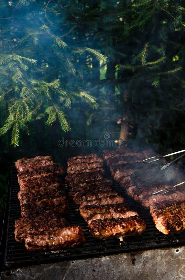 Gegrillte Hackfleischrollen nannten Mici, oder Mititei in der traditionellen rumänischen Küche kochte draußen an einem Sommertag  lizenzfreie stockfotografie
