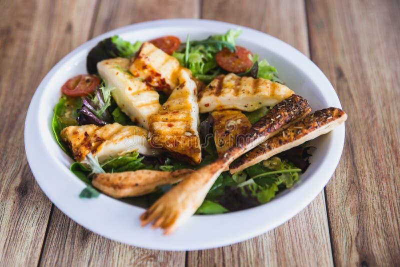 Gegrillte Halloumi-Käsesalathexentomaten und -kopfsalat in der weißen Platte im hölzernen Hintergrund Gesunde Nahrung lizenzfreie stockfotografie