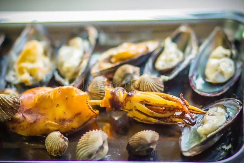 Gegrillte Kalmare, Miesmuscheln und Muscheln auf Holzkohlenofen nachts stellen gleich stockfoto