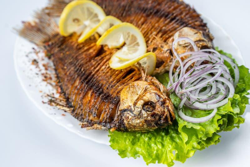 Gegrillte Karpfenfische auf der weißen Platte über Weiß stockbild