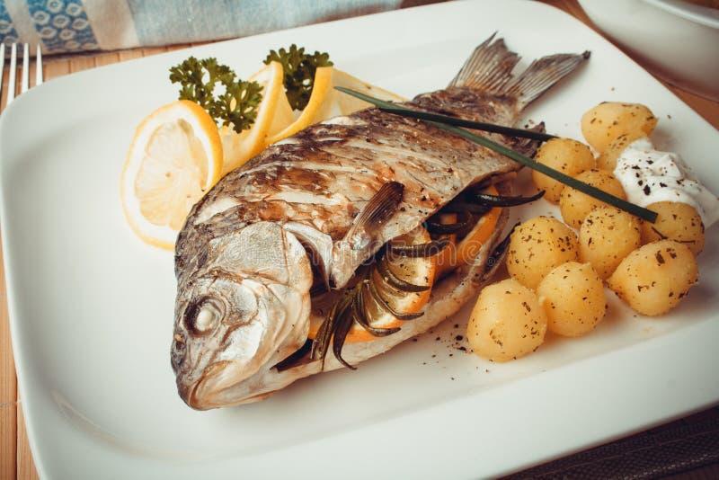 Gegrillte Karpfenfische mit Rosmarinkartoffeln und -zitrone stockfoto