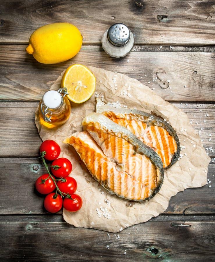 Gegrillte Lachse mit Tomaten und Zitrone lizenzfreies stockbild