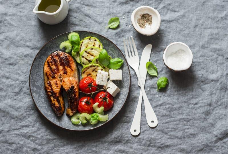 Gegrillte Lachse, Zucchini, backten Kirschtomaten und seidigen Tofu - gesunde ausgeglichene Mahlzeit auf grauem Hintergrund lizenzfreies stockfoto