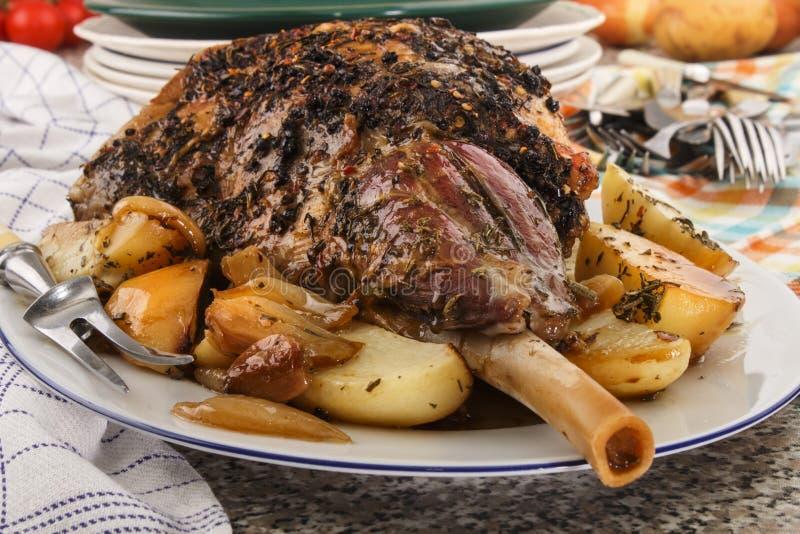 Gegrillte Lammkeule mit Rosmarin, Kartoffel und Zwiebel lizenzfreie stockbilder