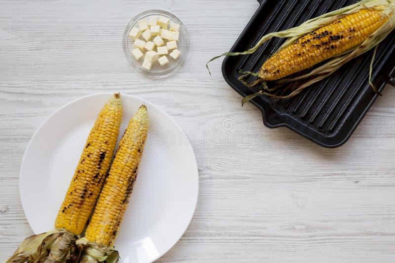 Gegrillte Maiskolben auf dem Grillen der Wanne und der weißen Platte, Butter, Draufsicht Von oben, lizenzfreie stockfotos