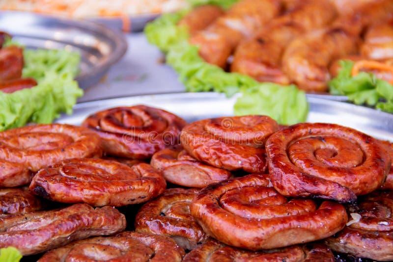 Gegrillte oder gebratene SpiralenSchweinswürste mit Rosmarin, Salz und peper auf Platte lizenzfreie stockbilder