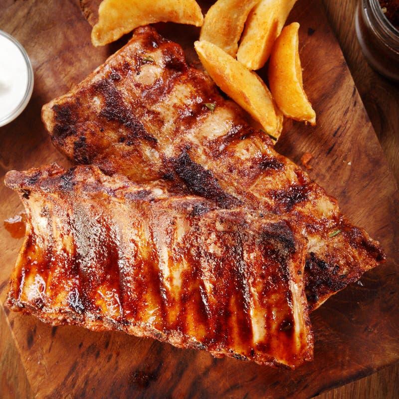 Gegrillte Schweinefleisch-Rippe auf Schneidebrett mit Kartoffeln stockfotos