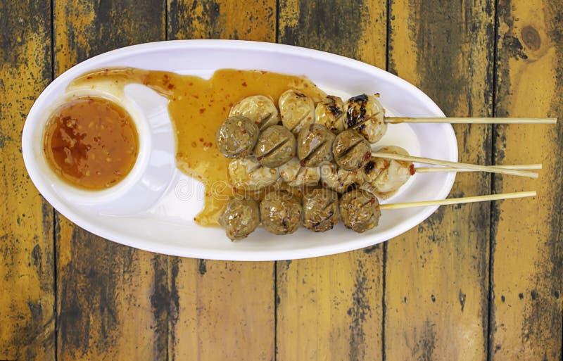 Gegrillte Schweinefleisch- und Rindfleischfleischklöschen mit Meeresfrüchtesoße auf weißer Plastikplatte stockfotos