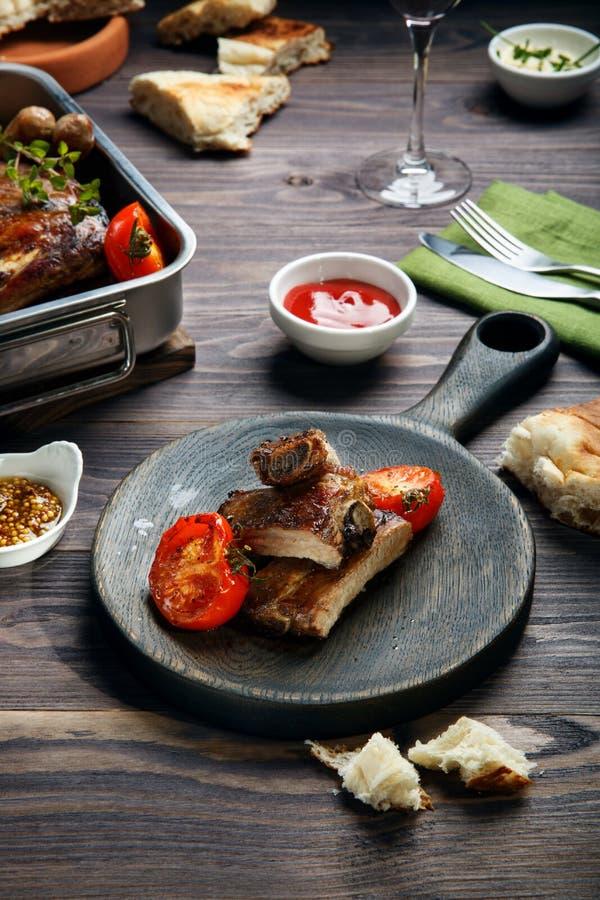 Gegrillte Schweinefleischrippen und -würste gedient mit Tomate und Soßen auf Holztisch lizenzfreie stockfotografie