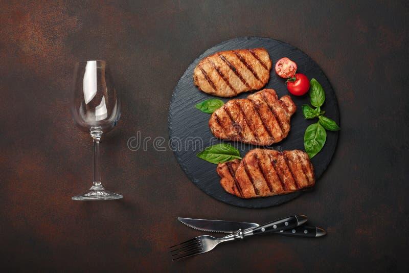 Gegrillte Schweinefleischsteaks mit Basilikum-, Tomaten-, Messer-, Gabel- und Weinglas auf schwarzem Stein und braunem rostigem H stockfotografie