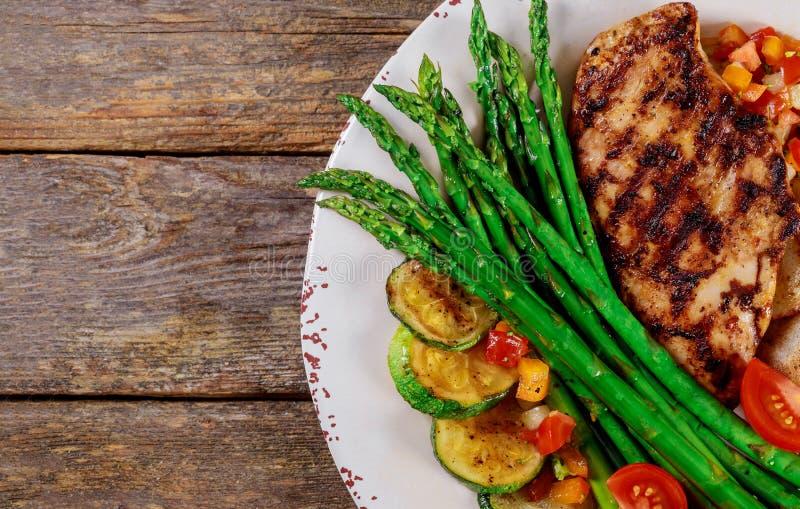Gegrillte Steaks, Kartoffelchips und Spargel auf weißer Platte lizenzfreie stockbilder