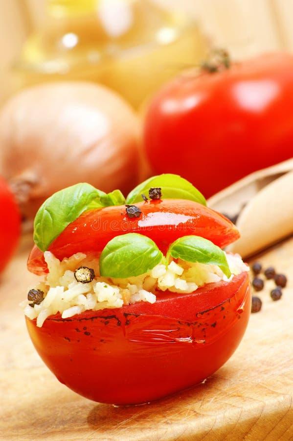gegrillte Tomate mit Reis auf einem Bauholzvorstand lizenzfreie stockfotos