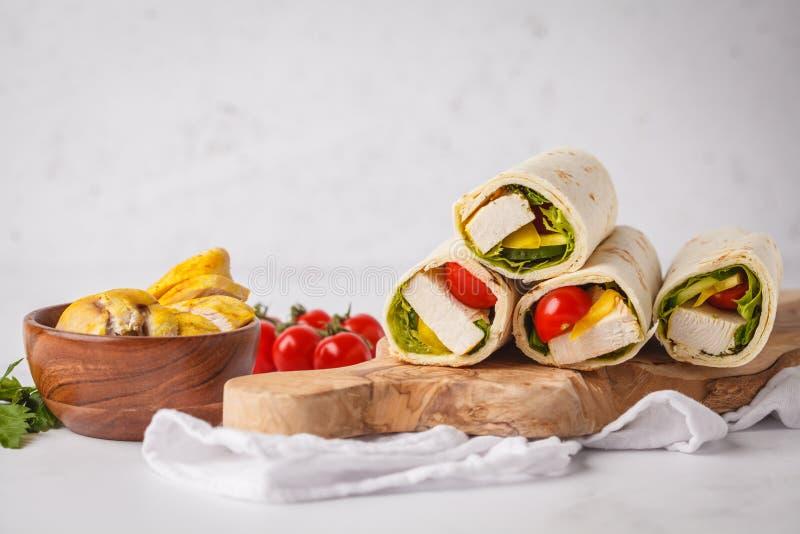 Gegrillte Tortillaverpackungen mit Huhn und Gemüse auf hölzernem BO lizenzfreie stockbilder