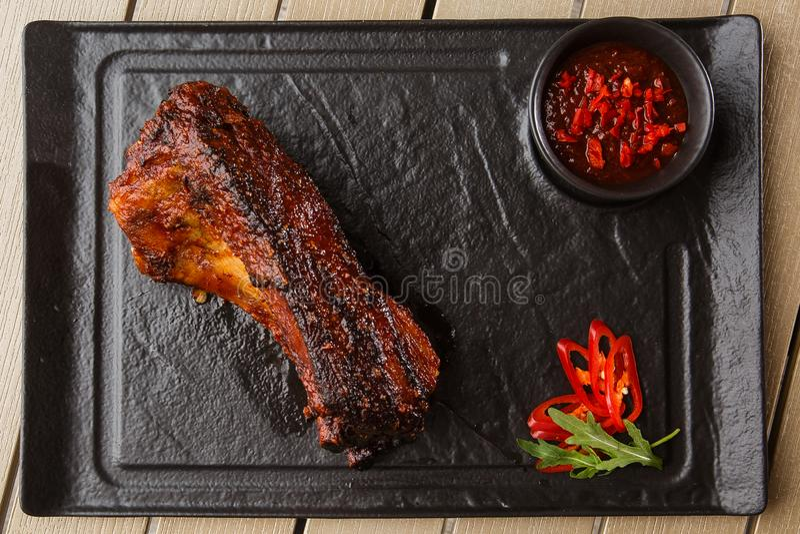 Gegrillte und heiße Schweinefleischrippen des Grills mit Pfeffer und scharfer Soße der heißen Paprikas auf schwarzem Steinhinterg lizenzfreie stockfotografie