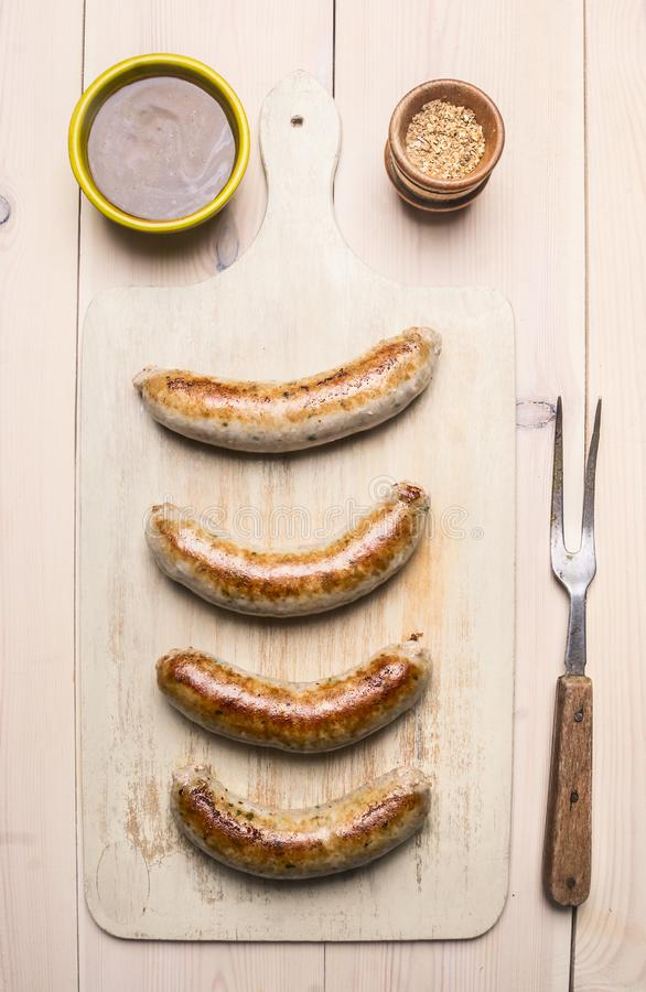 Gegrillte Würste mit einer Gabel grillten Fleisch, Soße und Gewürze auf Draufsicht des weißen rustikalen Hintergrundes lizenzfreies stockfoto