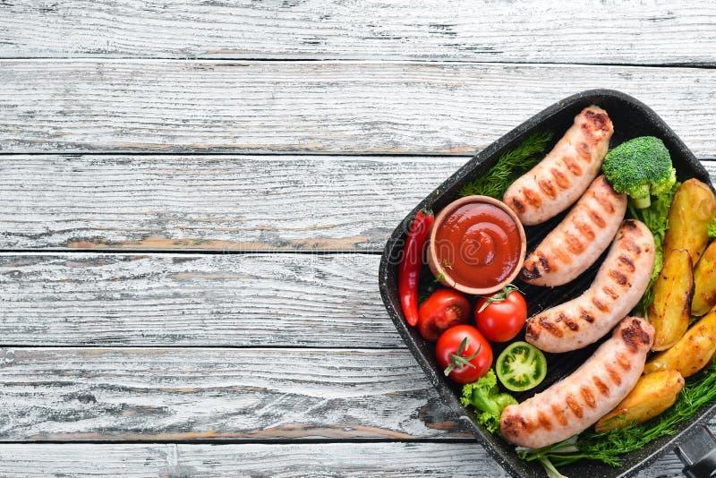 Gegrillte Würste mit Kartoffeln und Gemüse auf einem weißen hölzernen Hintergrund fleisch lizenzfreies stockbild